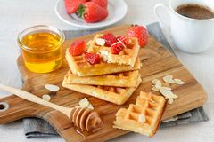 Colorful breakfast with waffles and strawberries. Healthy breakfast table with belgian waffles, exotic fruits and coffee Stock Photos