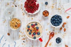 Healthy breakfast on the table: porridge, oats, berries, fruits, muesli Stock Photo