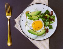 A healthy breakfast of toast with avocado, whole wheat bread and fried egg and burrito salad on white plate stock photo