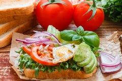 Healthy Breakfast - toast with egg, tomato, red onion, avocado, greens Royalty Free Stock Photo