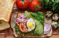 Healthy Breakfast - toast with egg, tomato, red onion, avocado, greens Stock Images