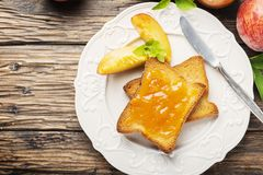 Healthy breakfast with toast and peach jam. Healthy summer breakfast with toast and peach jam, selective focus image and rustic style royalty free stock photography