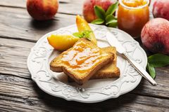 Healthy breakfast with toast and peach jam. Healthy summer breakfast with toast and peach jam, selective focus image and rustic style royalty free stock photo