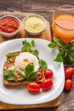 Healthy breakfast. Breakfast toast with poached egg, tomato sauce, basil and parmesan cheese on rustic wooden background Royalty Free Stock Images