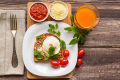 Healthy breakfast. Breakfast toast with poached egg, tomato sauce, basil and parmesan cheese on rustic wooden background Royalty Free Stock Photo