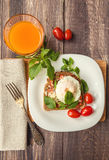 Healthy breakfast. Breakfast toast with poached egg, tomato sauce, basil and parmesan cheese on rustic wooden background Royalty Free Stock Image