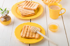 Healthy breakfast with toasted bread and honey near vase with flowers on white background. Yellow tone. Healthy breakfast with toasted bread and honey near vase stock photos