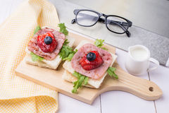 Healthy breakfast with toasted bread, milk, ham, vegetables, strawberry, jam and blueberry topping on wooden plate. Top view with Stock Photo