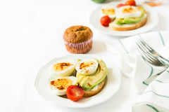 Healthy breakfast: toasts with avocado slices, tomato, paprika and eggs Stock Photography