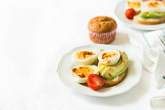 Healthy breakfast: toasts with avocado slices, tomato, paprika and eggs Stock Image