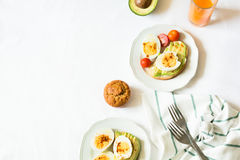 Healthy breakfast: toasts with avocado slices, tomato, paprika and eggs Royalty Free Stock Photo