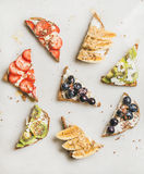 Healthy breakfast toasts with fruit, nuts, seed and cream cheese Royalty Free Stock Images