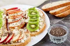 Healthy breakfast toasts with kiwi, apple, cottage cheese and chia seeds. On white plate and grey background.  Diet food. Vegan. Close up royalty free stock photos
