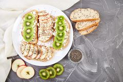 Healthy breakfast toasts with kiwi, apple, cottage cheese and chia seeds. On white plate and grey background. Top view, flat lay. Diet food. Vegan stock photos