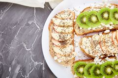 Healthy breakfast toasts with kiwi, apple, cottage cheese and chia seeds. On white plate and grey background. Top view, flat lay. Diet food. Vegan royalty free stock photo