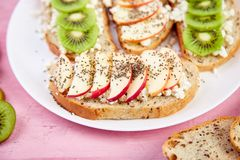 Healthy breakfast toasts with kiwi, apple, cottage cheese and chia seeds. On white plate and pink background. Close up. Diet food. Vegan royalty free stock photo