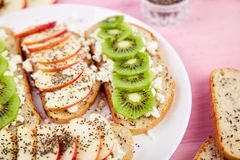 Healthy breakfast toasts with kiwi, apple, cottage cheese and chia seeds. On white plate and pink background. Close up. Diet food. Vegan royalty free stock photography