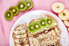 Healthy breakfast toasts with kiwi, apple, cottage cheese and chia seeds. On white plate and pink background. Top view, flat lay. Diet food. Vegan royalty free stock images