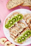 Healthy breakfast toasts with kiwi, apple, cottage cheese and chia seeds. On white plate and pink background. Top view, flat lay. Diet food. Vegan royalty free stock photography