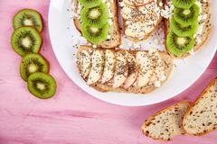 Healthy breakfast toasts with kiwi, apple, cottage cheese and chia seeds. On white plate and pink background. Top view, flat lay. Diet food. Vegan stock photography