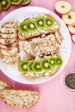 Healthy breakfast toasts with kiwi, apple, cottage cheese and chia seeds. On white plate and pink background. Top view, flat lay. Diet food. Vegan stock photos