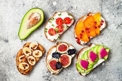 Healthy breakfast toasts with peanut butter, banana, chocolate granola, avocado, persimmon, chia seeds, figs Royalty Free Stock Photos