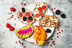 Healthy breakfast toasts with peanut butter, banana, chocolate granola, avocado, persimmon, figs. Healthy breakfast toasts with peanut butter, fruit toppings royalty free stock photos