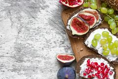 Healthy breakfast toasts. Wholegrain bread slices with cream cheese, various fruit, seeds and nuts Royalty Free Stock Images