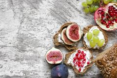 Healthy breakfast toasts. Wholegrain bread slices with cream cheese, various fruit, seeds and nuts. On wooden cutting board. Top viee Stock Image