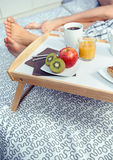 Healthy breakfast on tray and couple legs in Stock Image