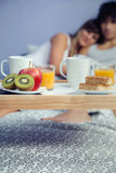 Healthy breakfast on tray and couple lying in Royalty Free Stock Image