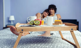 Healthy breakfast on tray and couple lying in. Healthy breakfast served on a wooden tray ready to eat and a happy couple in love hugging in the background Stock Photos