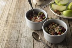 Healthy breakfast.Two bowls of muesli with oats, nuts and dried fruits - apples, resins, pumpkin seeds and almonds on wooden table stock photo