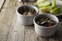 Healthy breakfast.Two bowls of muesli with oats, nuts and dried fruits - apples, resins, pumpkin seeds and almonds on wooden table stock photos