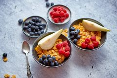 Golden cornflakes with fresh fruits of raspberries, blueberries and pear in ceramic bowl. Healthy breakfast for two is served. Golden cornflakes with fresh royalty free stock image