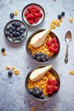 Golden cornflakes with fresh fruits of raspberries, blueberries and pear in ceramic bowl. Healthy breakfast for two is served. Golden cornflakes with fresh royalty free stock images