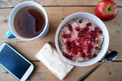 Healthy breakfast, vegetarian. Oatmeal with cranberries, apple, sandwich with cream cheese, tea, mobile phone. Stock Image