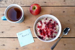 Healthy breakfast, vegetarian. Oatmeal with cranberries, apple, tea. royalty free stock image