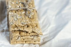 Healthy breakfast. Vitamin. Healthy snack: cereal crunchy multigrain Crispbread with flax seed, Oat Flakes on wrapping paper Backg. Close Up Healthy Snack Cereal royalty free stock photo