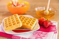 Healthy breakfast of waffles, strawberry, muesli and honey. Delicious healthy breakfast with fruit waffles and honey Stock Image