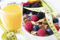 Bran cereal and orange juice with measuring tape Royalty Free Stock Image