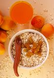 Healthy breakfast. White plate of oatmeal with dried apricots, a glass of an apricot juice and fresh apricots on a white. Table. Summer harvest royalty free stock photos