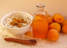 Healthy breakfast. White plate of oatmeal with dried apricots, a glass of an apricot juice and fresh apricots on a white. Table. Summer harvest stock images