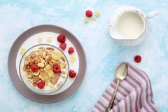 Healthy breakfast flakes with raspberries & milk on blue table. Stock Images