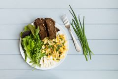 Healthy breakfast: whole wheat toasted bread, scrambled eggs, salads. Flat lay on grey wooden table royalty free stock photo