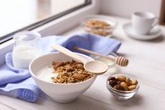 Healthy breakfast on window sill homemade granola with nuts. Healthy granola bars with nuts, seeds and dried fruits on white baking paper. Top view.Variety of Stock Photo