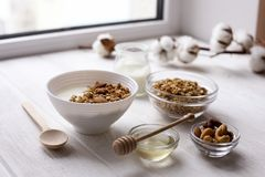 Healthy breakfast on window sill homemade granola with nuts. Healthy granola bars with nuts, seeds and dried fruits on white baking paper. Top view.Variety of Royalty Free Stock Photo