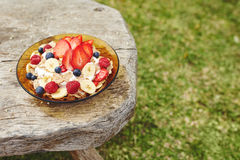 Healthy breakfast on wooden table. Strawberries, blueberries and breakfast cereal in yogurt on a wooden rustic table with copy space royalty free stock images