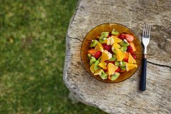 Healthy breakfast on wooden table. Top view of a fresh fruit salad with strawberries kiwi orange and papaya on wooden table with copy space stock photography