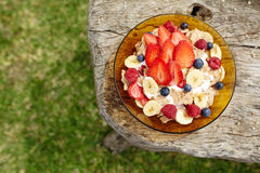 Healthy breakfast on wooden table. Yogurt, cereals and cornflakes with fresh berries and banana with copy space. Top view royalty free stock photo